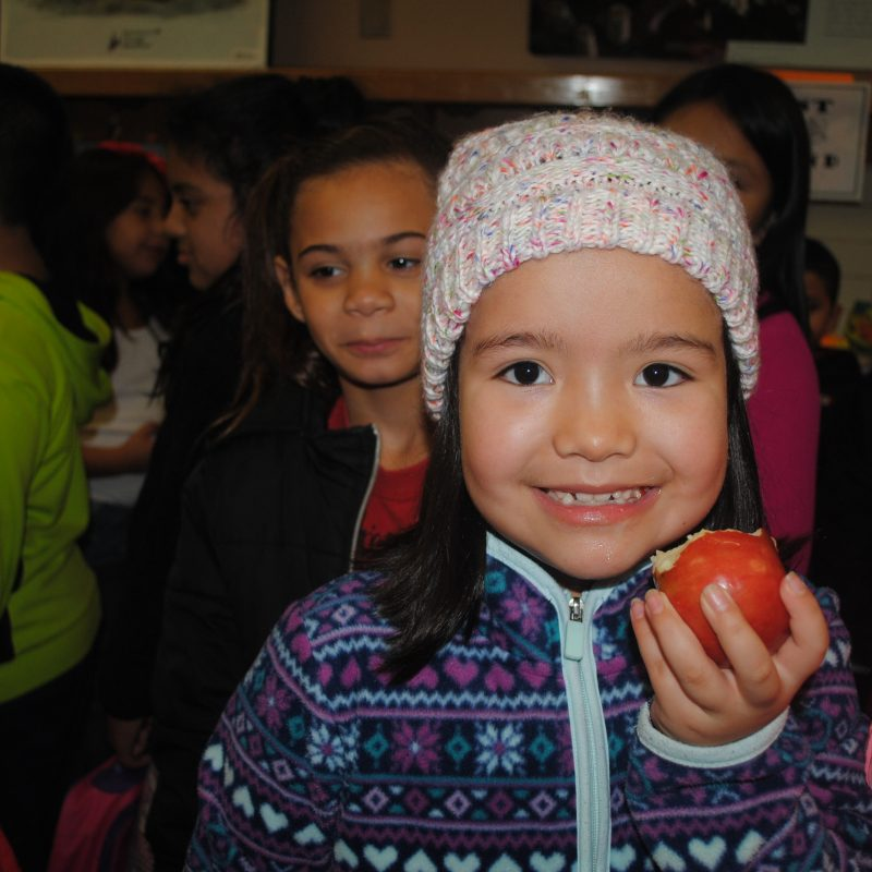Girl enjoys an apple during the Great Apple Crunch.